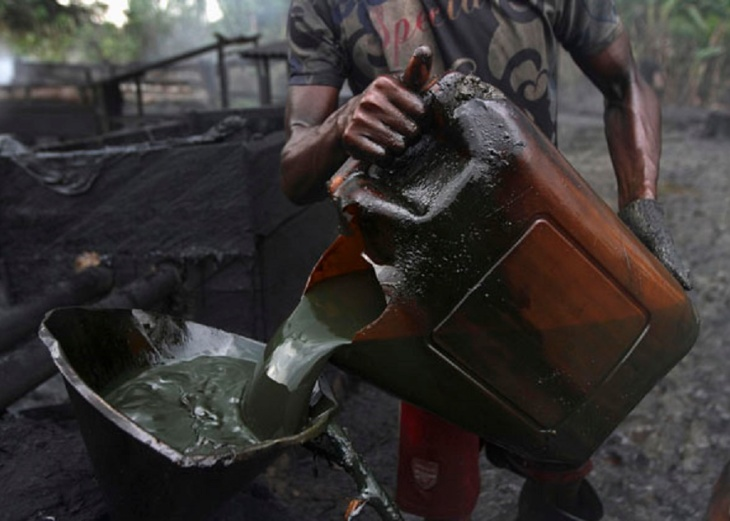 A worker pours crude oil into a locally made burner using a funnel at an illegal oil refinery site